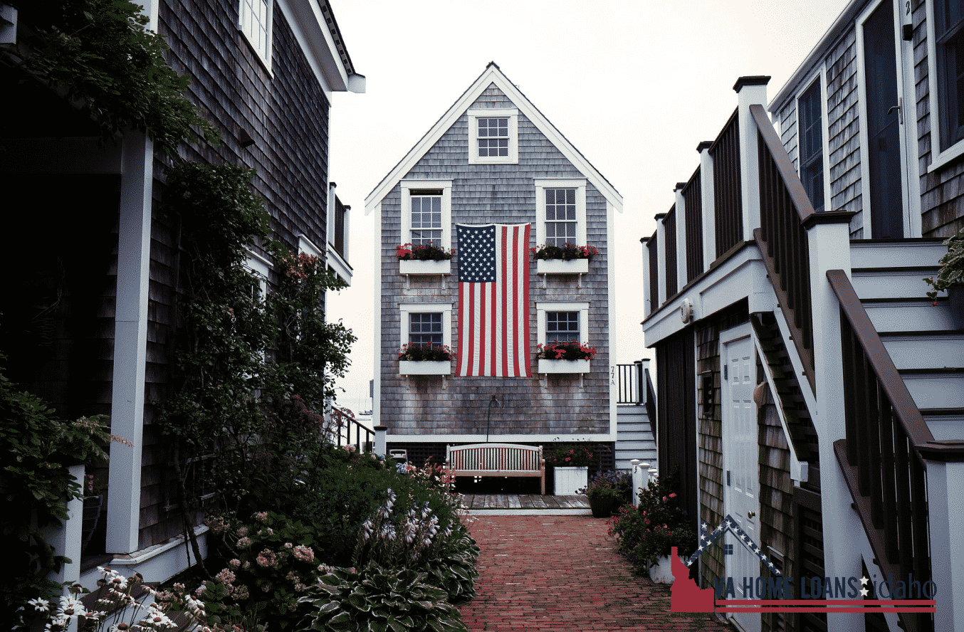 Tall and skinny grey house with an american flag hung on the front of it.