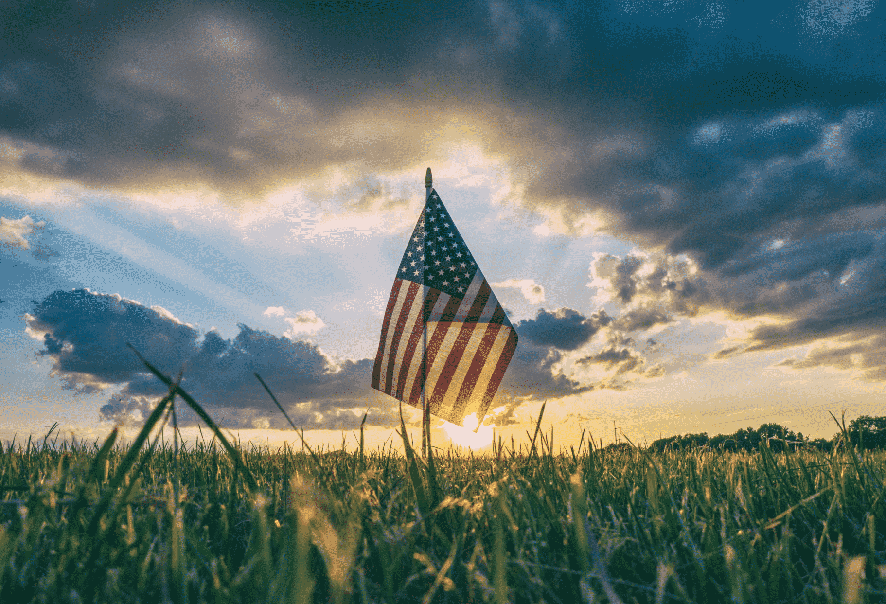 An American flag atop a pole in a green grassy field with the sun rising behind it.