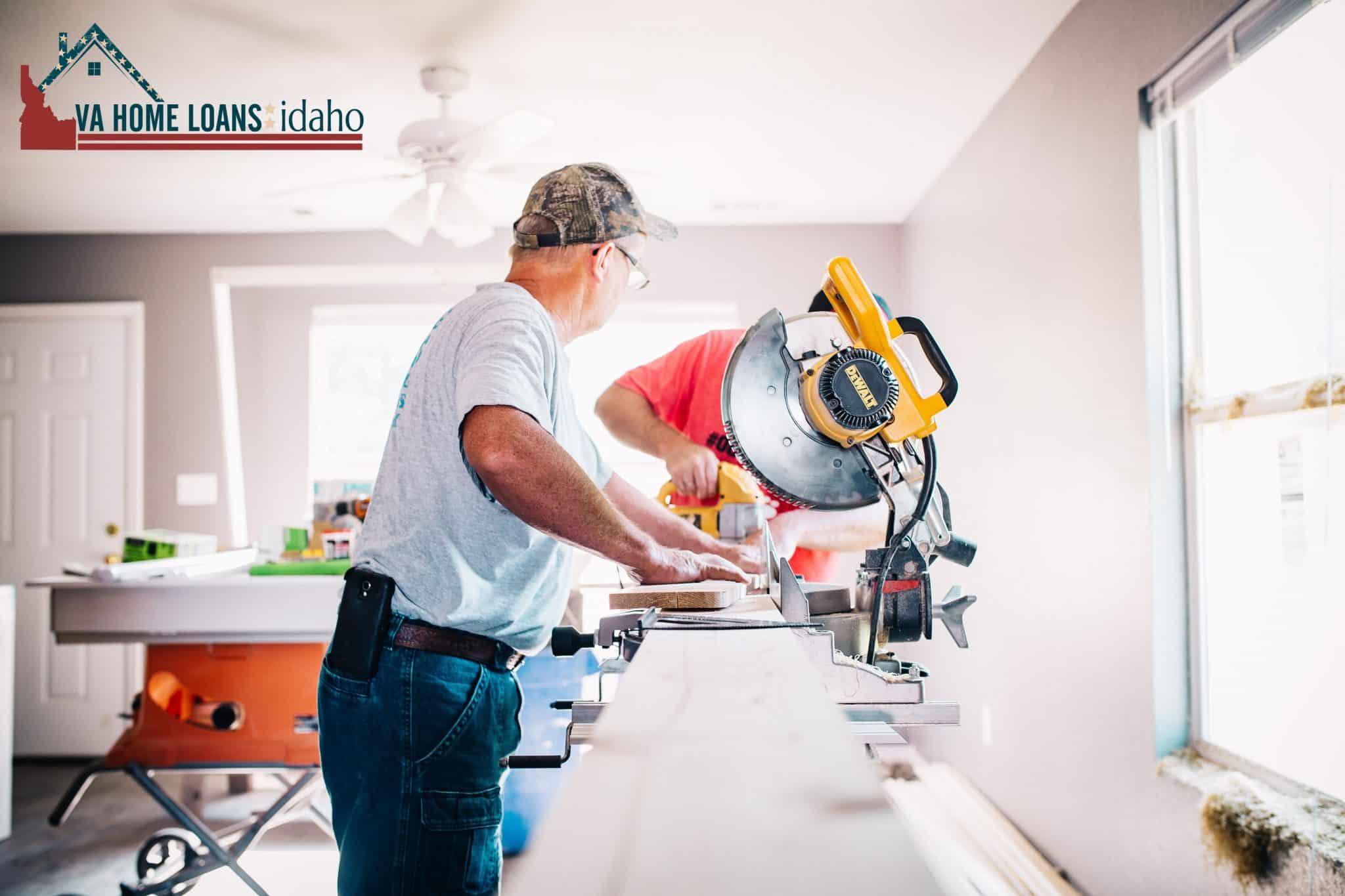Man in grey shirt cutting wood with a saw.
