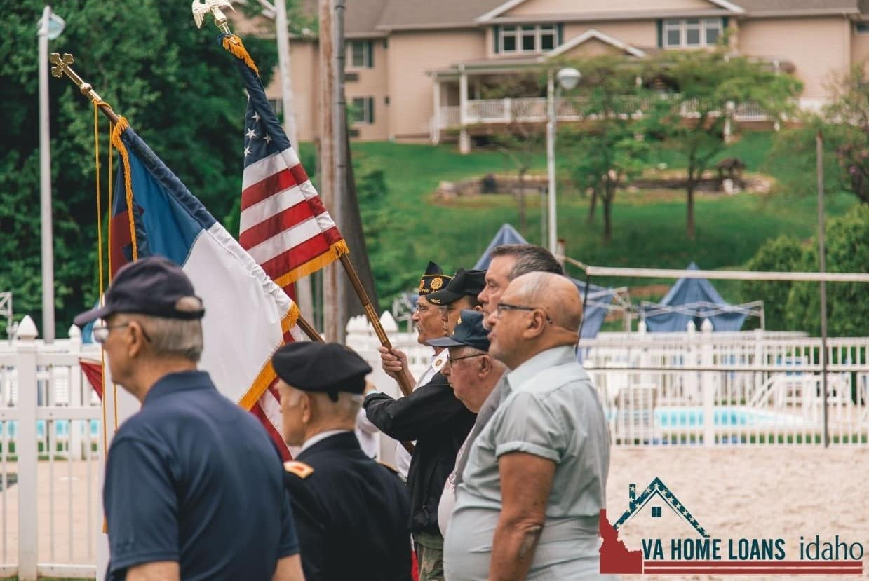Veterans standing in a line with two flags