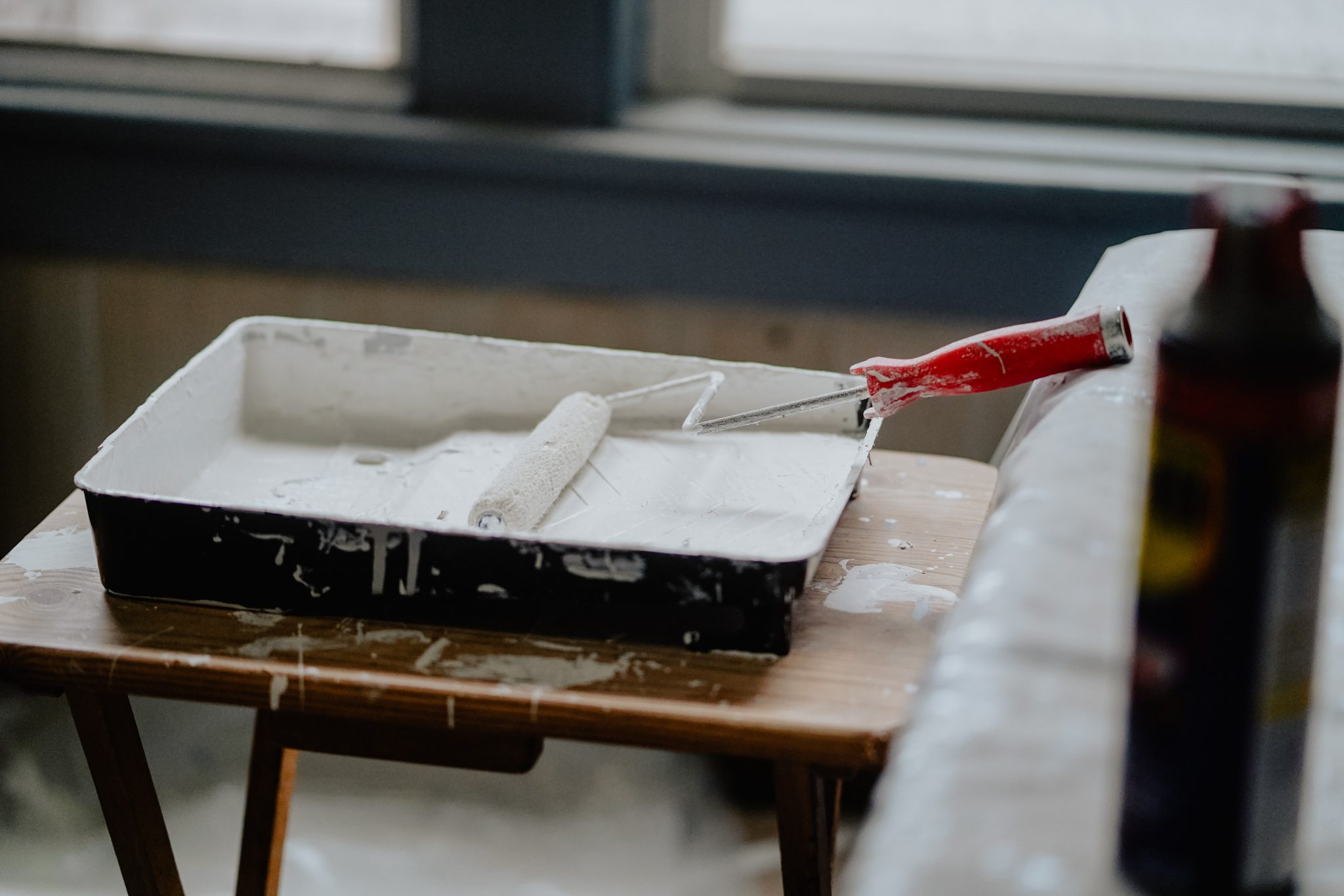 Close up of a white paint roller sitting on a wood table